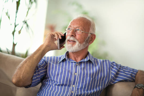 senior man chatting on a mobile phone at home - using phone stock photos and pictures