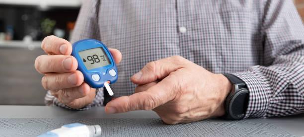 seniorenmann überprüft blutzuckerspiegel zu hause - hyperglycemia stock-fotos und bilder