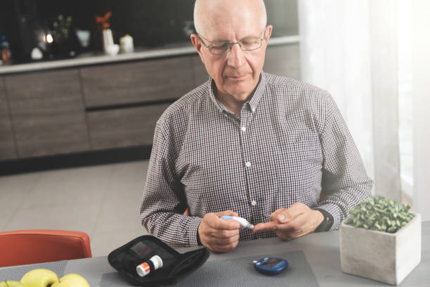 Senior man checking blood sugar level at home Senior man with glucometer checking blood sugar level at home. Diabetes, health care concept lancet arch stock pictures, royalty-free photos & images