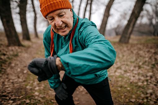 Senior man checking heart rate monitor after jogging