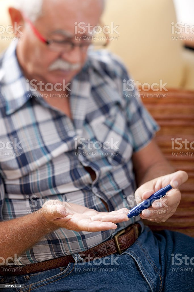 A senior man checking his blood sugar royalty-free stock photo