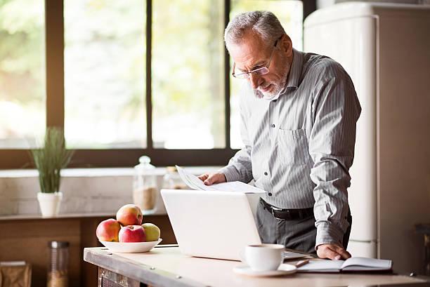 senior man checking his papers in kitchen at home - seniorenwohnungen stock-fotos und bilder