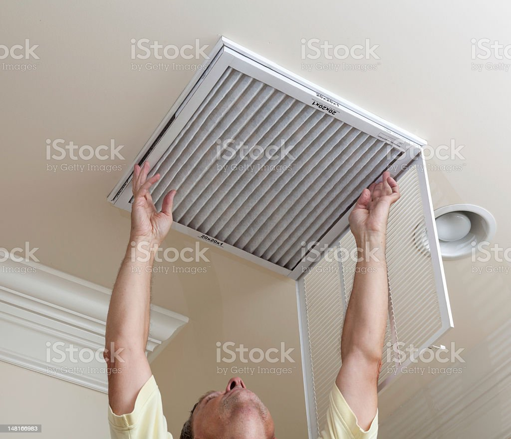 A senior man checking the air conditioner filter royalty-free stock photo