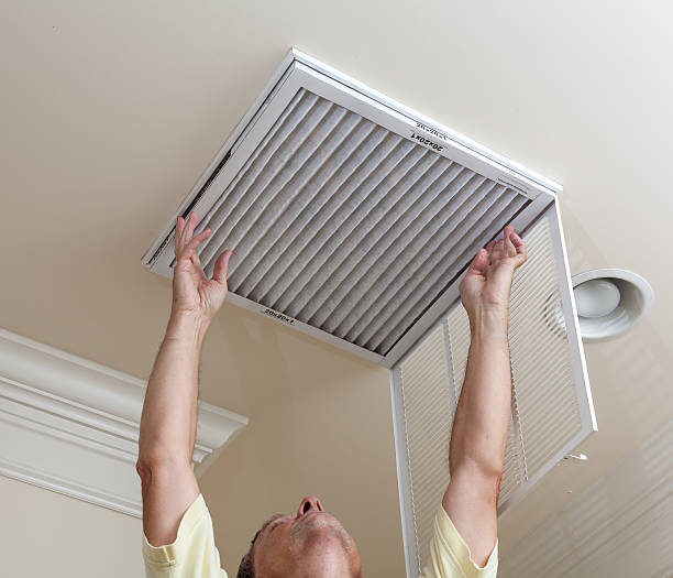 A senior man checking the air conditioner filter stock photo