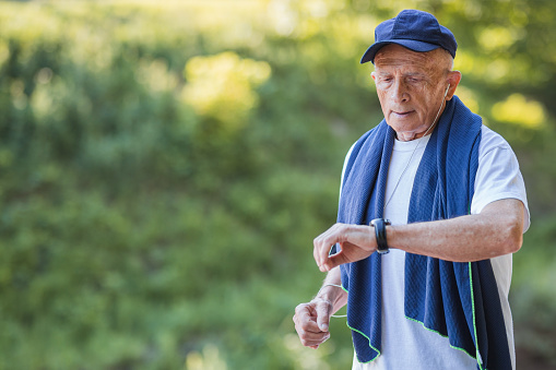 Senior man checking the time when jogging