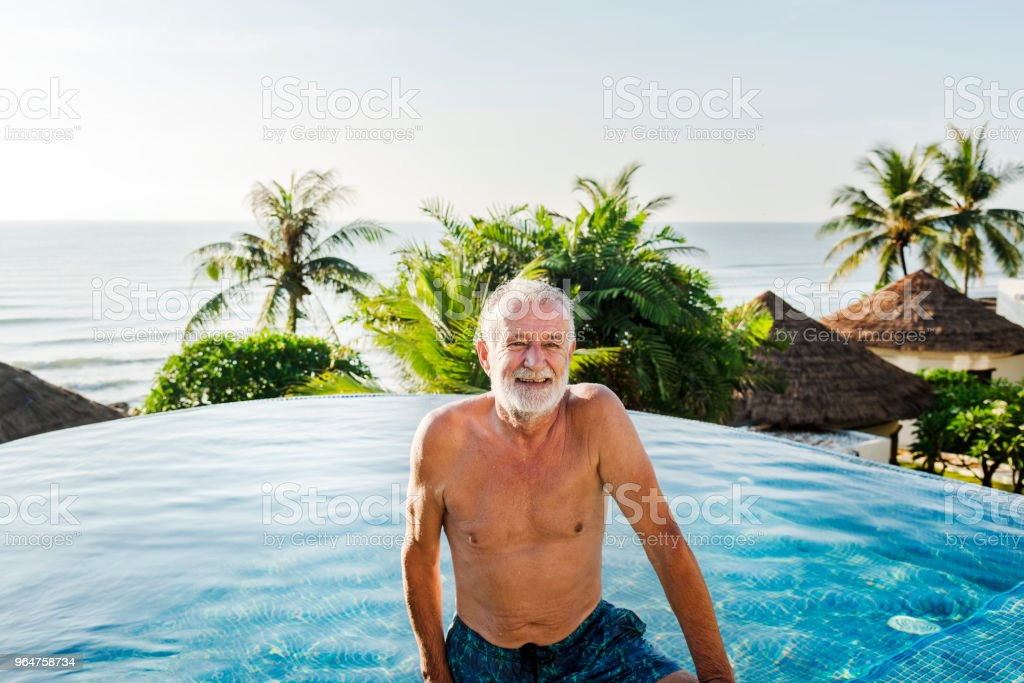 Senior man chilling in swimming pool royalty-free stock photo