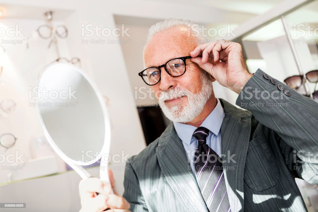Senior man choosing wearing glasses in optical store stock photo