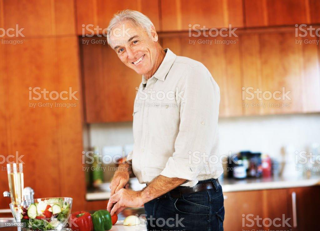 Senior man chopping vegetables royalty-free stock photo