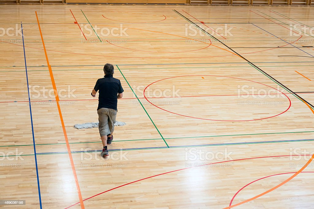 Senior man cleaning the floor in a new school gymnasium with new...