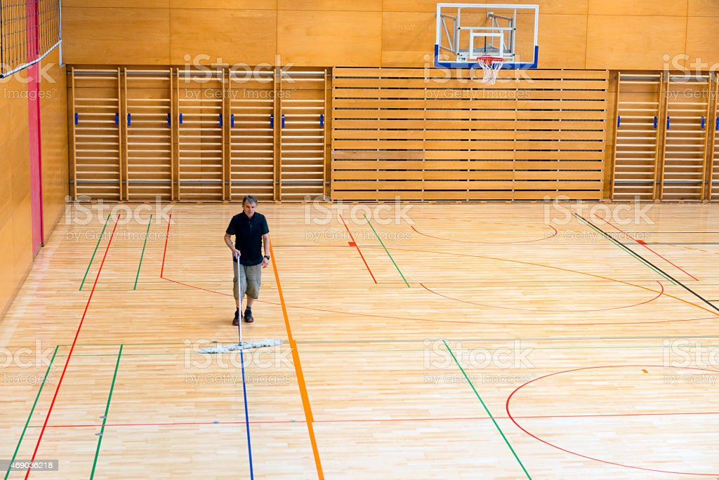 Senior man cleaning the floor in a new school gymnasium with...