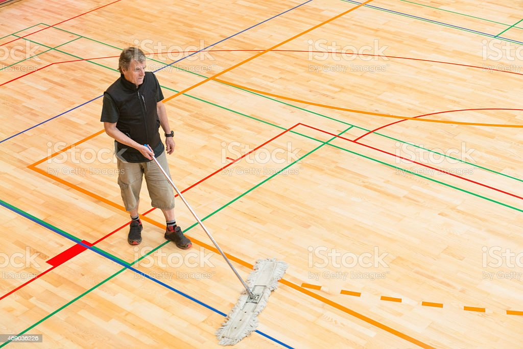 Senior man in shorts and black T-shirt cleaning the floor in a new...