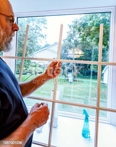 A senior adult man is at home working on his domestic chores. He is using a spray bottle and paper towels to spray, wash, scrub and clean the back yard view dining room window panes, as well as the removable wooden trim grid moldings from each section of the three sided bay window.