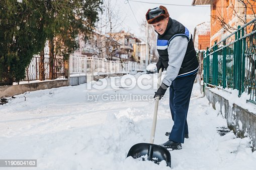 Senior man is cleaning snow in front of his home in a suburban city street.