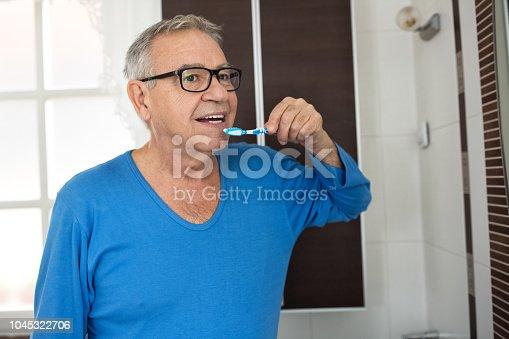 Senior man cleaning teeth with toothbrush at nursing home