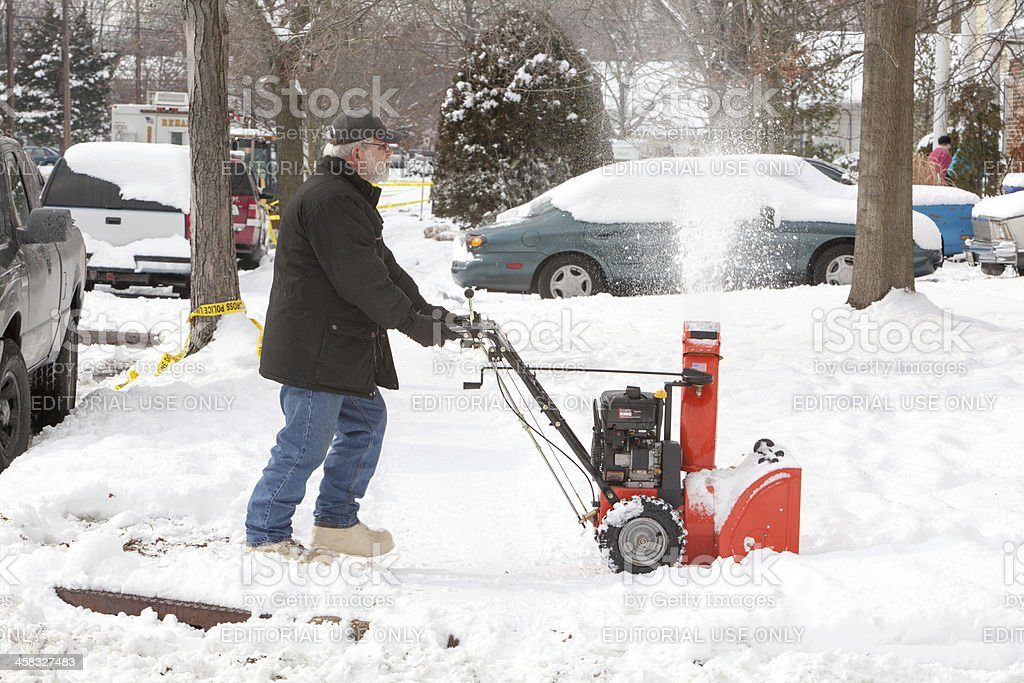 Senior man clearing snow with a snowblower  RM stock photo