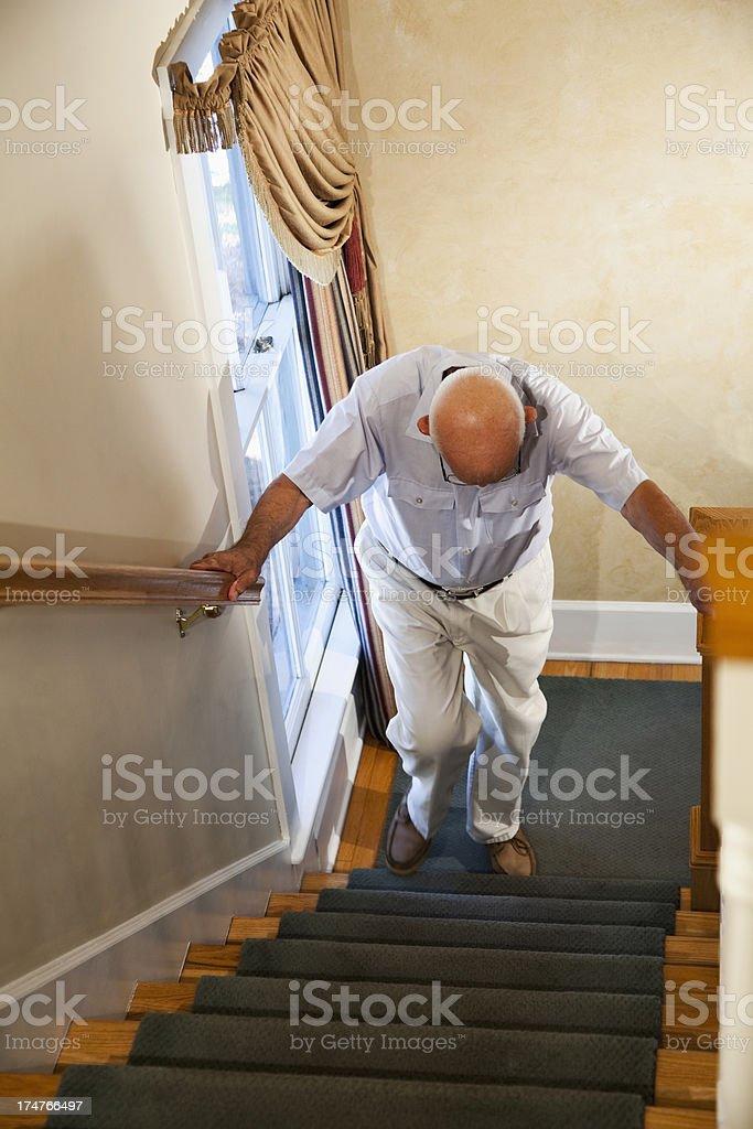 Senior man climbing stairs stock photo