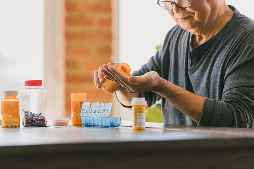 A retired senior man pours pills from a pill bottle into his hand as he organizes the medication into a weekly pill organizer.