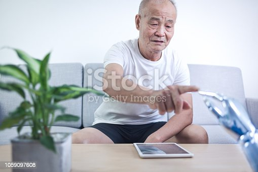 istock Senior man connecting robot indoors 1059097608