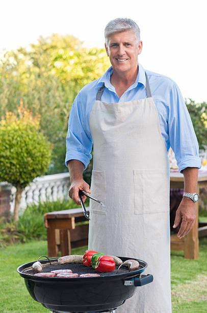 alter mann kochen barbecue - grillschürze stock-fotos und bilder