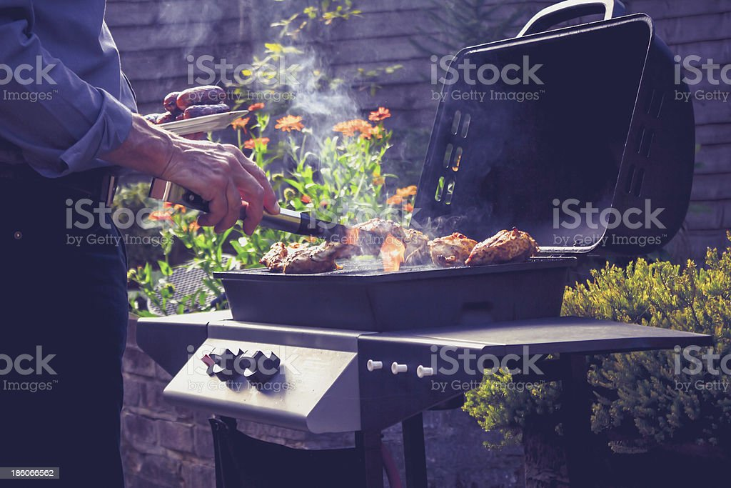 Senior man cooking meat on barbecue stock photo