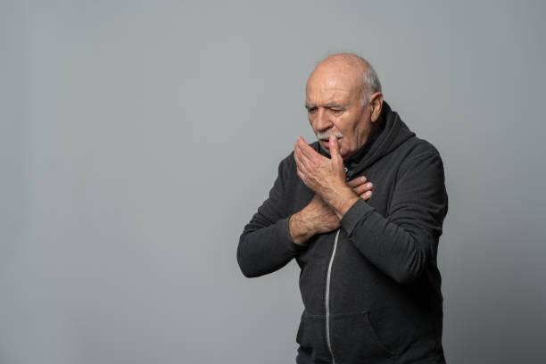senior mann hustet in die hand, isoliert auf weißem hintergrund - einzelner senior stock-fotos und bilder