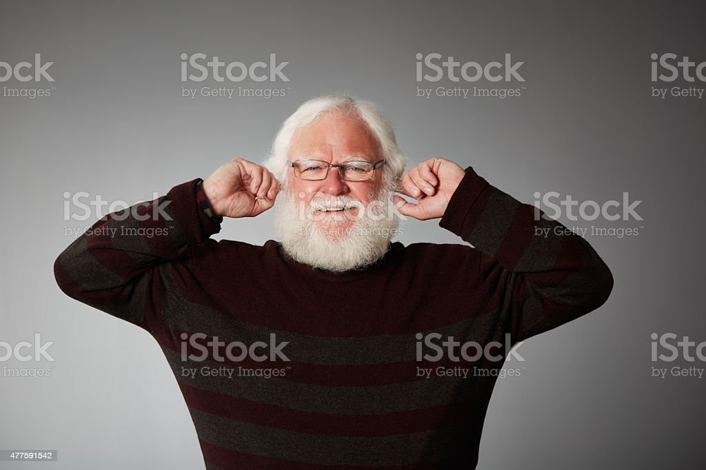 Senior man covering ears to block the noise stock photo