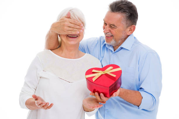 senior man covering woman's eyes and holding heart-shaped box - senior valentine stock photos and pictures