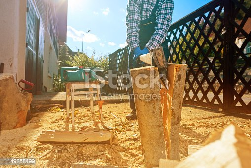 unrecognizable senior man cutting logs in sunny day, working in the garden.