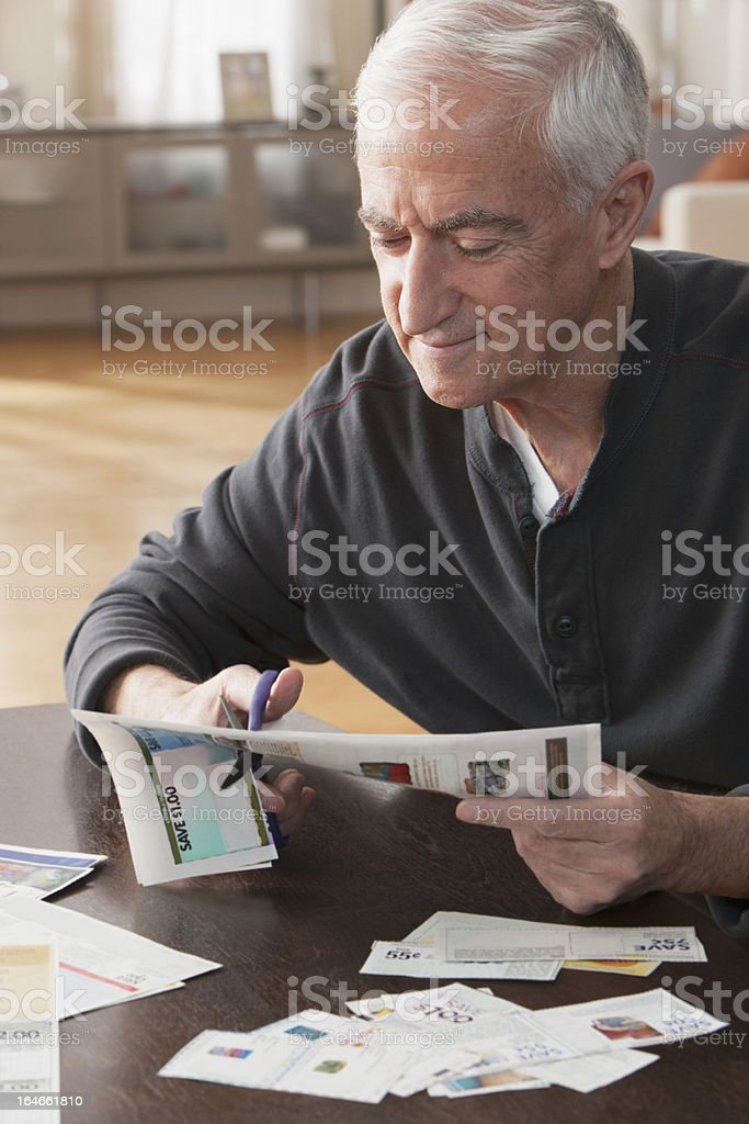 Senior man cutting out coupons stock photo
