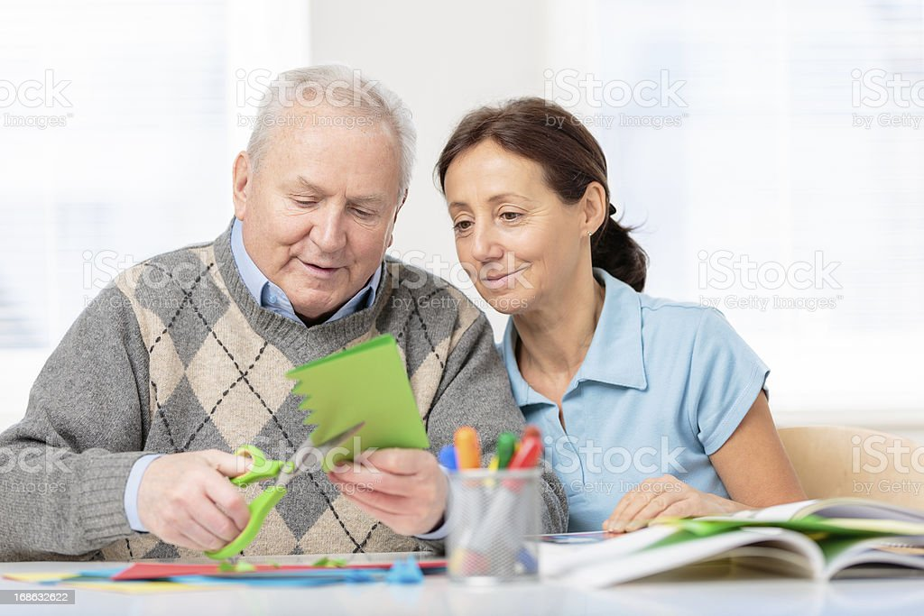 Senior man cutting paper with scissors royalty-free stock photo