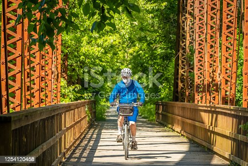 Senior man bicycling along converted railroad bridge on sunny summer day in Midwestern state park wearing a protective face mask; trees in background