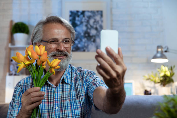 Senior man dating online holding a flower Happy retired man making distant video call on mobile phone, sitting on sofa. Long distance relationship. long distance relationship stock pictures, royalty-free photos & images