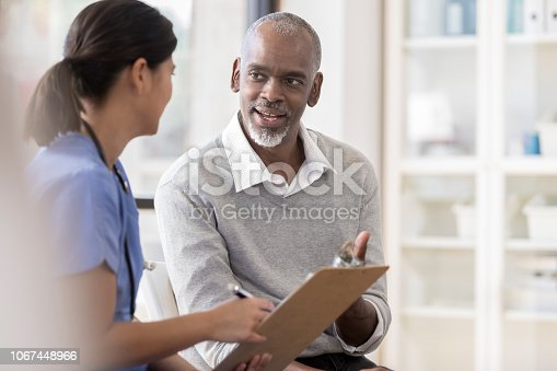 A cheerful senior man sits next to an unrecognizable female doctor in her office.  She holds a clipboard as he asks questions regarding his diagnosis.