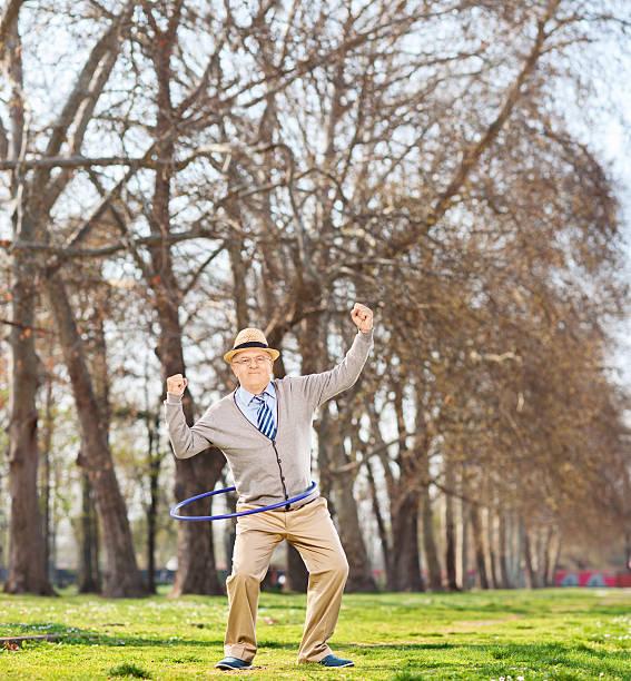 alter mann, die einen hula-hoop-übung im park - hula hoop workout stock-fotos und bilder