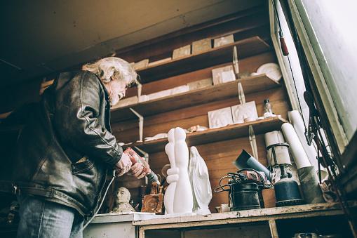 Senior man doing art work in the garage