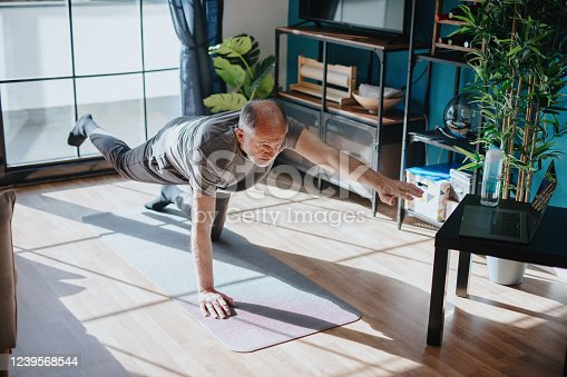 Senior man doing balance exercise, watching youtube videos and learning the exercises