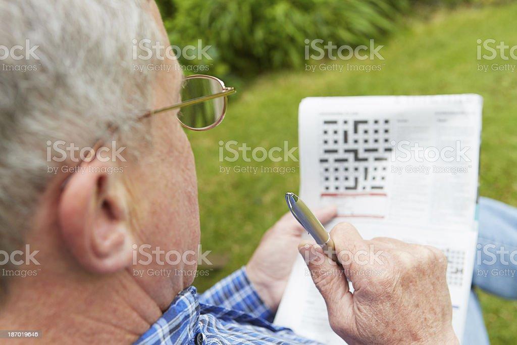 Senior Man Doing Crossword Puzzle In Garden stock photo