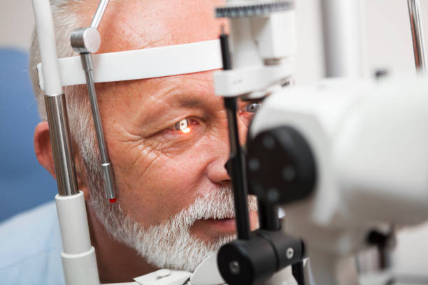 senior man doing eye test with ,close up - optical instrument stock pictures, royalty-free photos & images