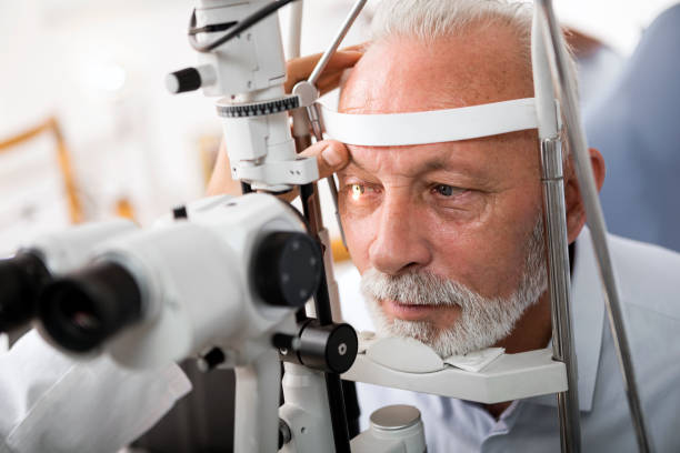 Senior man doing eye test with optometrist Doctor Checking Patient's Eyes optical instrument stock pictures, royalty-free photos & images