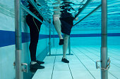 Senior man doing physical therapy in the water with the help of a physiotherapist - medical concepts
