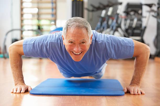 Senior Man Doing Press Ups In Gym stock photo