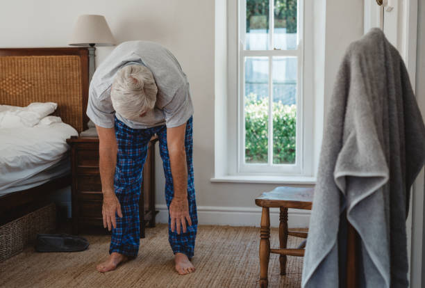 Senior man doing stretches after waking up in the morning Senior man in pajamas stretching to touch his toes while waking up in his bedroom in the morning touching toes stock pictures, royalty-free photos & images