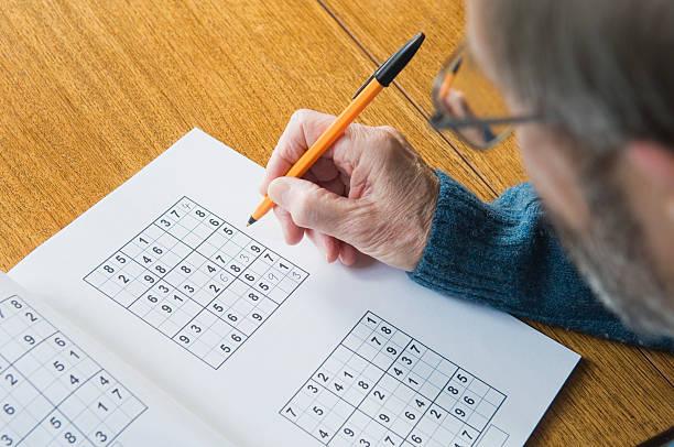Senior man doing sudoku puzzle stock photo
