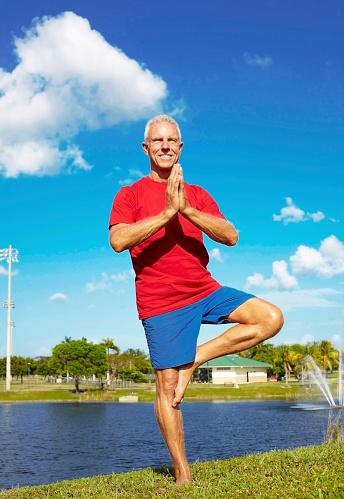 senior man doing yoga tree pose at lakeshore stock photo