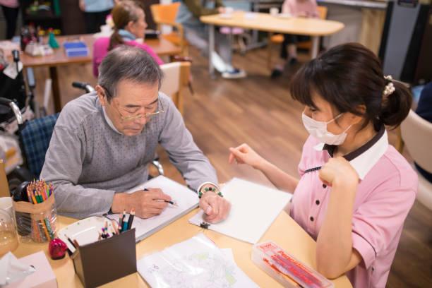 年配の男性が女性の看護師で絵を描く - 高齢者介護 ストックフォトと画像