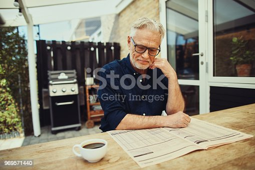 116379055 istock photo Senior man drinking coffee and reading a newspaper outside 969571440