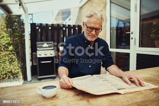 116379055 istock photo Senior man drinking coffee and reading a newspaper outside 969571512