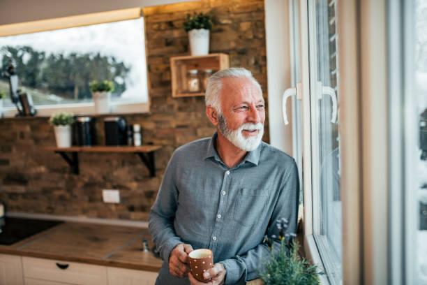 수석 남자는 부엌에서 커피를 마시는 창 겨울 날에 보고. - 창문 너머로 봄 뉴스 사진 이미지