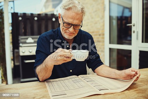 116379055 istock photo Senior man drinking fresh coffee and reading a newspaper outside 969571588