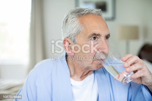 Close-up of retired senior man drinking water in bedroom. Male is sitting at home. He is in nightwear.